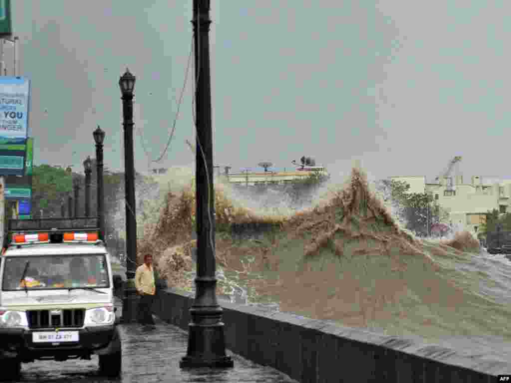 A police vehicle patrols along the promenade as a large wave breaks during high tide near the landmark Gateway of India monument in Mumbai on June 16. The monsoon, which covers most of agriculture-dependent India from June to September, has advanced halfway across the country and is expected to be robust in the current year following a crippling drought in 2009. (AFP)
