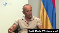 Former Armenian President Robert Kocharian being interviewed after he was charged with crimes.