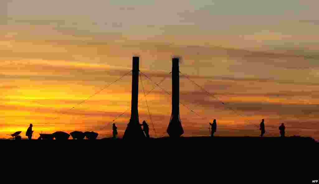 Laborers add coal to the fire and adjust smokestacks in a traditional Afghan brick factory near Mazar-e Sharif. (AFP/Qais Usyan)