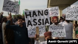 Supporters of Tehrik-e Labaik Pakistan, a hard-line religious political party, hold placards as they march during a protest in Rawalpindi on October 12.