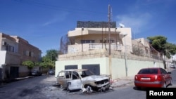 Поврежденный автомобиль у здания российского посольства в Ливии через день после атаки. Триполи, 3 октября 2013 года.
