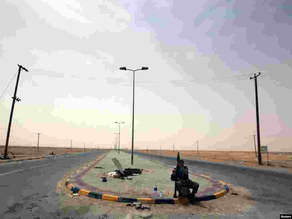 A rebel fighter armed with a rocket-propelled grenade (RPG) controls an intersection at the western gate of Ajdabiyah, Libya Photo by Yannis Behrakis for Reuters.