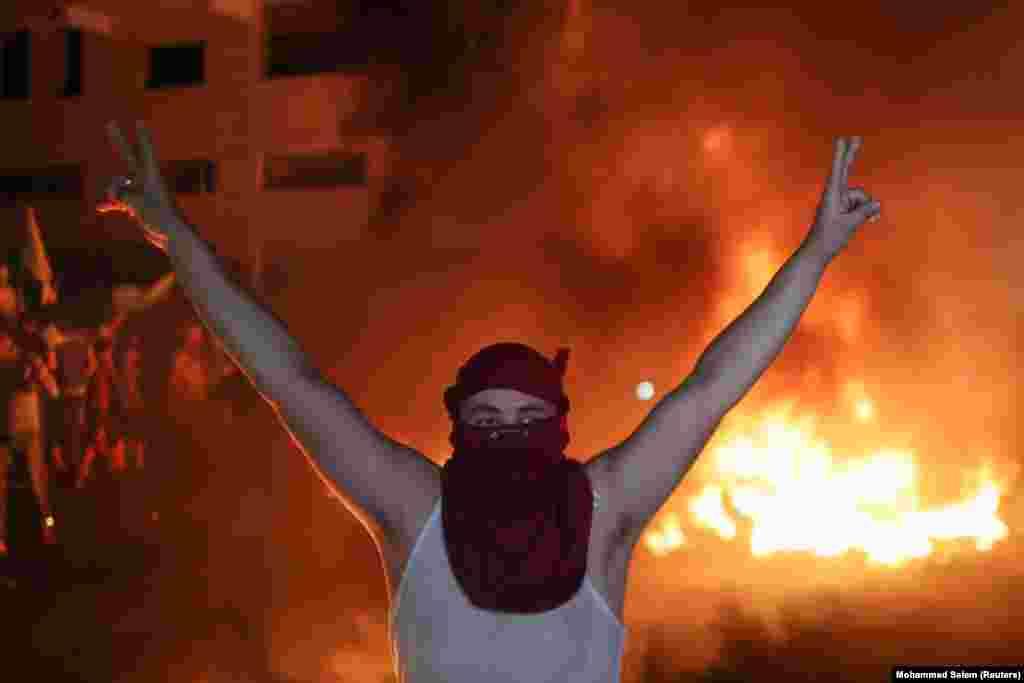 Hatalmas lángcsóvak előtt emeli a magasba a kezét az egyik palesztin tiltakozó.