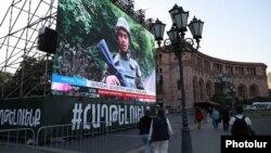 На большом экране, установленном на Площади Республики в Ереване, показывают репортаж государственного телевидения о войне в Нагорном Карабахе. 9 октября 2020 года.