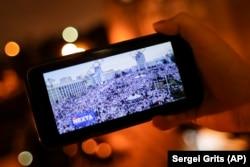 """Egy felhasználó a NEXTA élő Telegram-csatornája közvetítését nézi egy minszki demokráciapárti tüntetésről, 2020. augusztus 19-én. A Telegram alkalmazás nélkülözhetetlen eszköze lett a tömegtüntetéseket koordináló belarusz ellenzékieknek. A Koalíció a biztonságos webért nevű amerikai civil szervezet azonban januárban pert indított az App Store ellen, azt követelve, hogy az alkalmazást töröljék a kínálatból. Mindez azután történt, hogy Trump volt amerikai elnök hívei behatoltak a Capitoliumba. A felperes szerint a Telegram """"fehér felsőbbrendűségiek, neonácik és mások gyűlöletkeltő tartalmait"""" közvetíti. Május 24-ig az App Store nem törölte a Telegramot."""