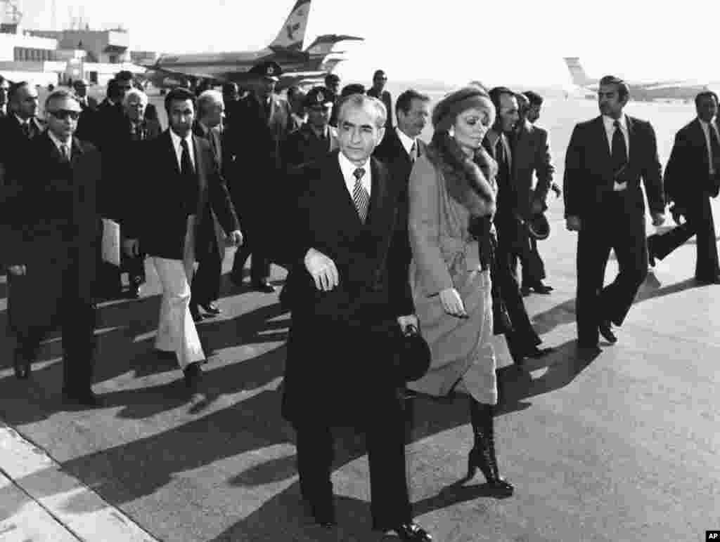 "Iran's Shah, Mohammad Reza Pahlavi, and his wife, Empress Farah, walk on the tarmac at Mehrabad Airport in Tehran to board a plane on January 16, 1979. The Shah left Iran for what was officially a vacation. Many Iranians rejoiced with chants of ""The Shah is gone!"" The man who had ruled the country for 37 years would never return from exile, dying some 13 months later."