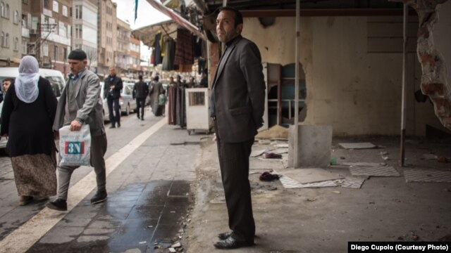 Faruk Taylan stands inside his damaged store, where he once sold shoes and clothes in the Sur district of Diyarbakir.