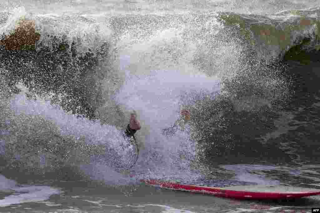 A surfer crashes off a wave at Charmouth, in Dorset, southern England after a major storm hit the region, forcing hundreds of thousands of evacuations and interrupting transportation.