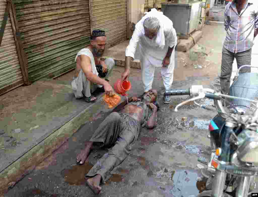A man helps a heatstroke victim at a market area in Karachi.