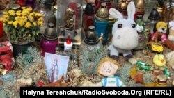 Біля будинку, де трапилась 28 серпня вночі трагедія, лампадки, квіти, м'які іграшки