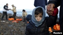 Greece -- A Syrian refugee child looks on, moments after arriving on a raft with other Syrian refugees on a beach on the Greek island of Lesbos, January 4, 2016