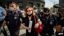 "Russian police officers in Moscow detain a supporter of Ivan Safronov, a former journalist who was detained on ""treason"" charges earlier this week."