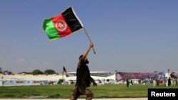 An Afghan man holds an Afghanistan national flag during a ceremony marking the country's 96th Independence Day in Jalalabad on August 19.