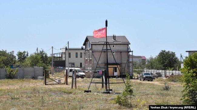 На геодезическом знаке триангуляционного пункта вывешен красный флаг с наименованием воинской части времен войны