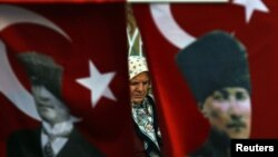 A woman wearing a traditional head scarf is framed by Turkish flags depicting the founder of modern Turkey in Istanbul. (file photo)