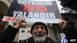 "Turkey - A Turkish man holds a placard reading ""Genocide is a lie"" in front of the French Consulate in Istanbul to protest against a law, voted the day before by French MPs, that outlaw denial of the 1915 Armenian genocide in Ottoman Turkey, 23Dec2011"