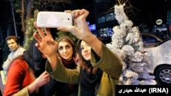 Жаңа жыл қарсаңында шырша қасында суретке түсіп жатқан Иран әйелдері. Тегеран, 22 желтоқсан 2015 жыл.