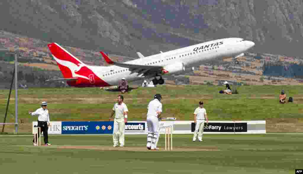 A Qantas jet takes off above the cricketers during the first day of the four-day warm-up international cricket match between New Zealand and England in Queenstown, New Zealand. (AFP/Marty Melville)