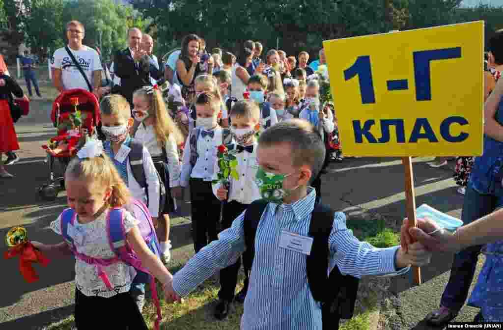 Першокласники у захисних масках біля будівлі школи в День знань у столиці України, 1 вересня 2020 року. Цього дня за парти у Києві сіли більш як 30 тисяч першокласників