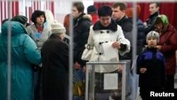 Женщина опускает в избирательную урну бюллетень во время референдума о статусе Крыма. Симферополь, 16 августа 2014 года.