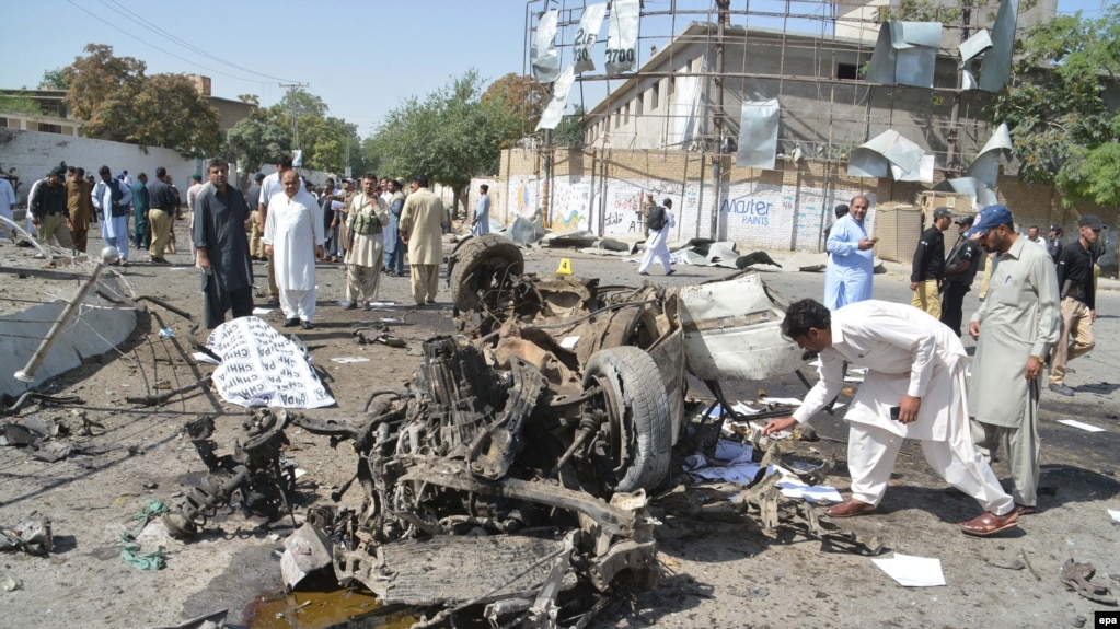 Pakistani security officials inspect the scene of a blast near the inspector-general of police office in Quetta on June 23.
