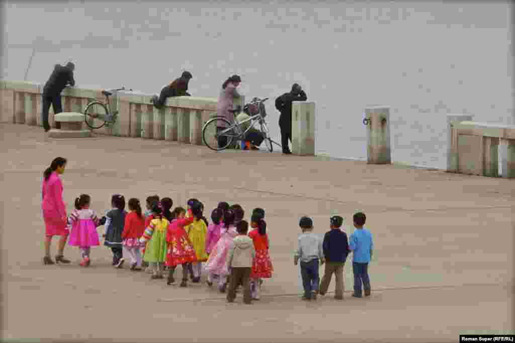 Детский сад на прогулке вдоль набережной. Зачем мужчина пытается прыгнуть в воду – мы не знаем