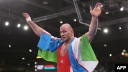 Uzbekistan's Artur Taymazov celebrates after defeating Georgia's Davit Modzmanashvili in their men's 120-kilogram gold-medal match during the wrestling event of the London 2012 Olympics.