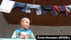 Ребенок стоит на крыльце, где сушится детское белье. Ошская область Кыргызстана.