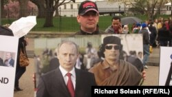 A protester holds up a photo of Vladimir Putin and Muammar Qaddafi in front of the White House on March 31, 2011.