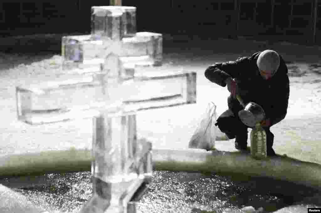 A man bottles holy water from a pool under an Orthodox cross made of ice during a ceremony to celebrate Epiphany in Tyumen, Russia. (Reuters/Eduard Korniyenko)