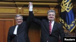 Ukrainian President Petro Poroshenko (right) raises aloft the hand of his Polish counterpart Bronislaw Komorowski during a session of the parliament in Kyiv on April 9.