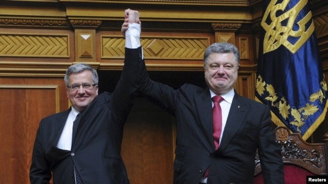 Ukrainian President Petro Poroshenko (right) raises aloft the hand of his Polish counterpart Bronislaw Komorowski during a session of the parliament in Kyiv on April 9.
