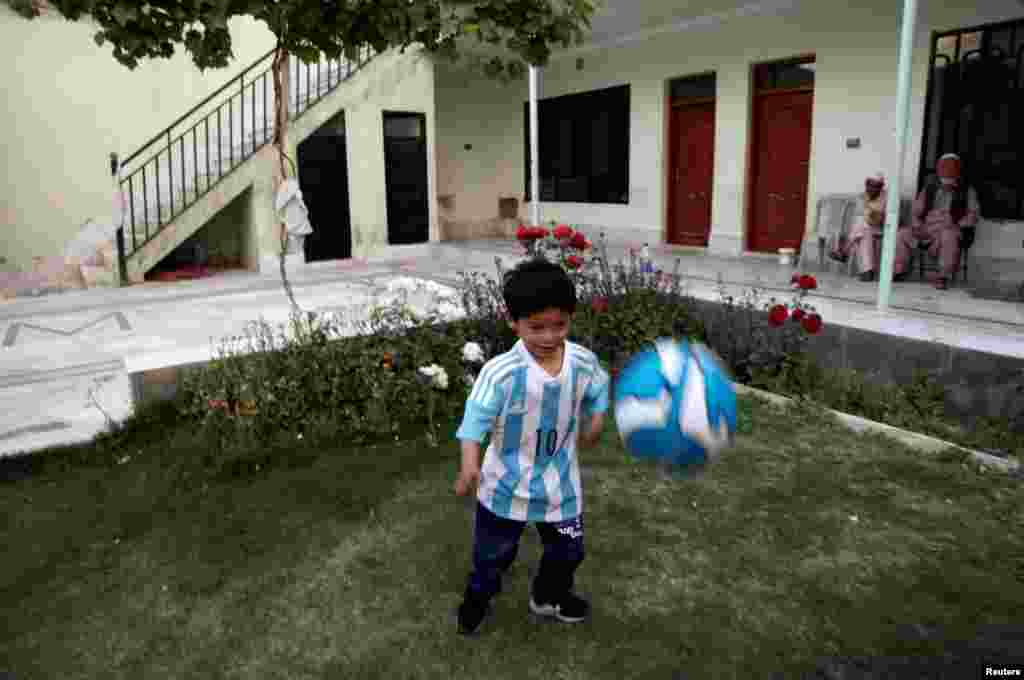 Five-year-old Murtaza Ahmedi, a Lionel Messi fan from Afghanistan, wears a shirt signed by Barcelona star Lionel Messi as he plays with a football at his relatives' home in Quetta, Pakistan, on May 3. Murtaza's family had to leave Afghanistan because of kidnapping fears following constant telephone threats. (Reuters/Naseer Ahmed)