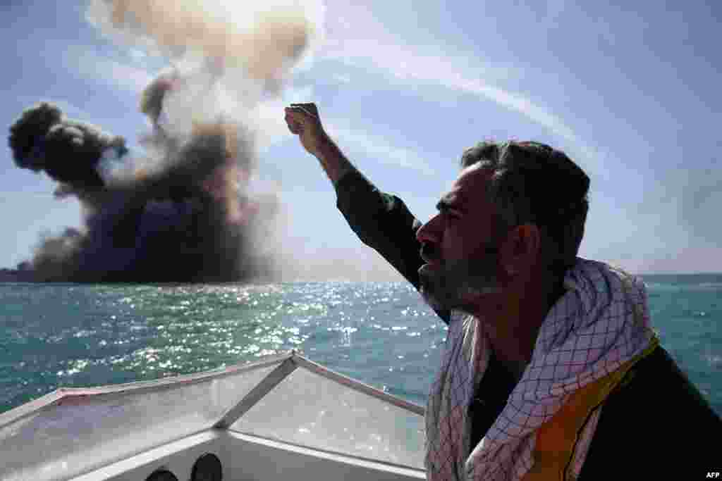 A member of Iran's elite Revolutionary Guards chants slogans after attacking a naval vessel during a military drill in the Strait of Hormuz in southern Iran on February 25. (AFP/Hamed Jafarnejad)