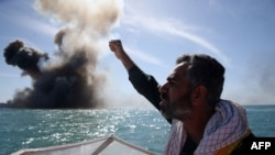 Iran -- A member of Iran's elite Revolutionary Guards chants slogans after attacking a naval vessel during a military drill in the Strait of Hormuz in southern Iran, February 25, 2015