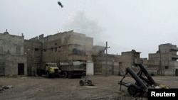 Free Syrian Army fighters fire a homemade mortar at Karm al-Tarab neighborhood in Aleppo on January 27.