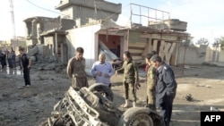 Residents look at the remains of several car bombs that exploded in the northern Iraqi city of Kirkuk on November 14.