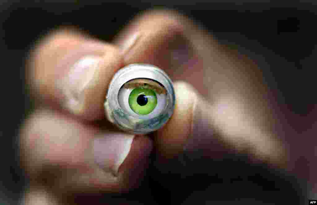 A worker holds a spare doll's eye at a workshop in Duesseldorf, Germany. (AFP/Martin Gerten)