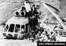 Афганські моджагеди снідають біля уламків збитого ними радянського вертольота