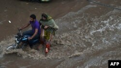 Pakistani residents travel through floodwaters following heavy rain in Lahore on July 14.