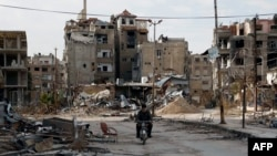A man drives his motorbike past damaged buildings in Harasta, east of the Syrian capital, Damascus, on February 10.