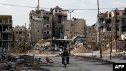 Мотоциклист едет по разрушенной улице в Дамаске, столице Сирии. Иллюстративное фото.