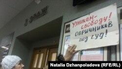 Активистка с плакатом в поддержку обвиняемых