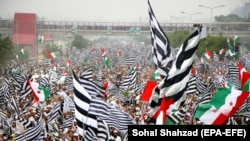 Supporters of opposition political parties wave party flags in Islamabad on November 1.