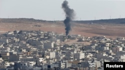 Smoke rises after a U.S.-led air strike on the Syrian town of Kobani on October 8.