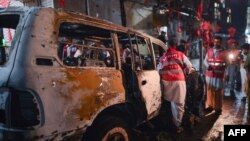 Pakistani volunteers search a destroyed vehicle at the site of a suicide bomb attack at an election campaign rally in Peshawar on April 16.
