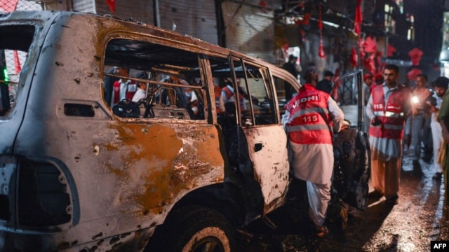 Pakistani volunteers search a destroyed vehicle at the site of a suicide-bomb attack at an election campaign rally in Peshawar on April 16.