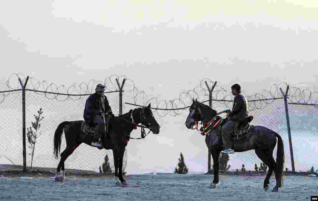 Two Afghans ride horses on the outskirts of Kabul. (epa/Hedayatullah Amid)