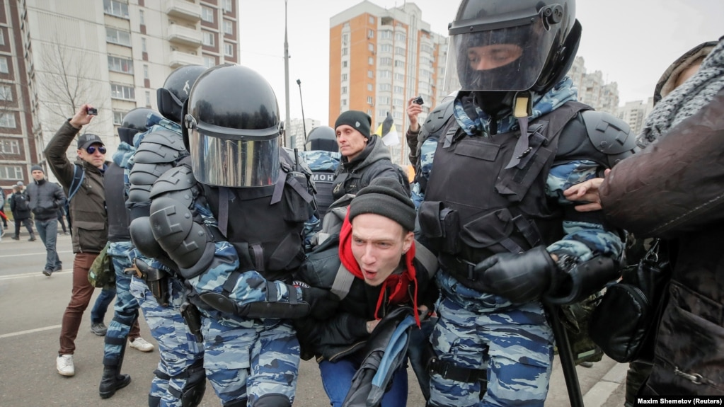 Police detain protesters at the nationalist march in Moscow.