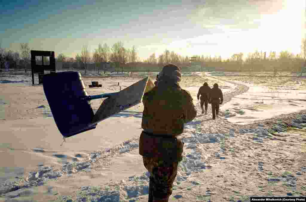Soldiers spend the day clearing snow off the shooting range using a plywood contraption seen here.